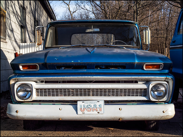 A blue mid-1960's Chevrolet C/K pickup truck with a Chevrolet USA-1 license plate on the front bumper. in the small town of Burr Oak, Michigan.