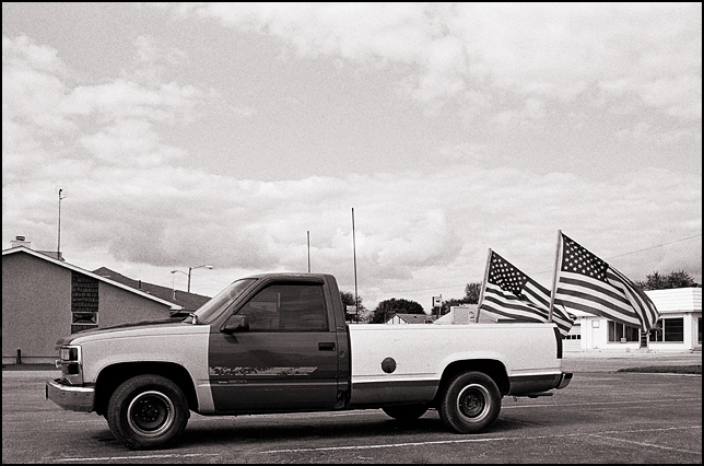 A Chevrolet pickup truck with two large American flags flying from the back of the bed in the small town of Churubusco, Indiana.