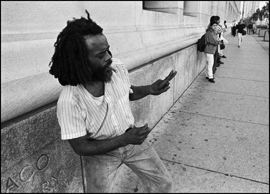 An African American man with dreadlocks dances on the sidewalk while smoking a cigar in front of the Chicago Public Library on Michigan Avenue in Chicago.