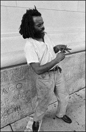 A black man with dreadlocks smokes a cigar and dances on the sidewalk on Michigan Avenue in Chicago.