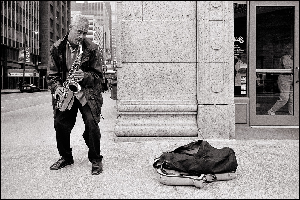 An elderly African-American street musician plays his saxophone on Chicago's Michigan Avenue.
