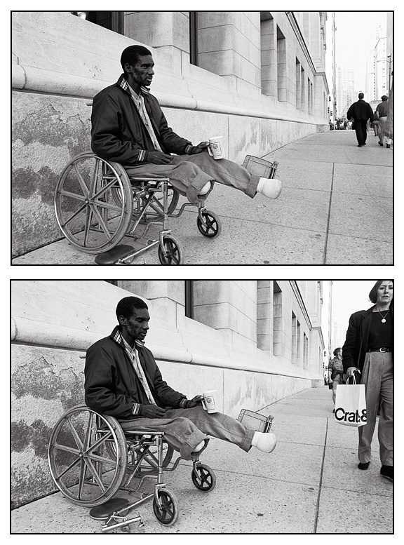 A disabled black man panhandles from his wheelchair on Michigan Avenue in Chicago while a wealthy woman carrying a crate & barrel bag walks past without looking at him.