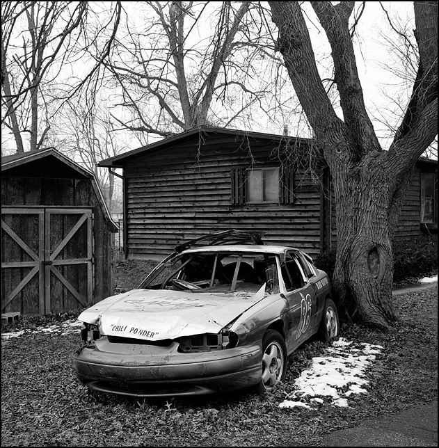 A wrecked Chevrolet Lumina race car with front end collision damage sits behind a house on Arbor Avenue in Fort Wayne, Indiana.