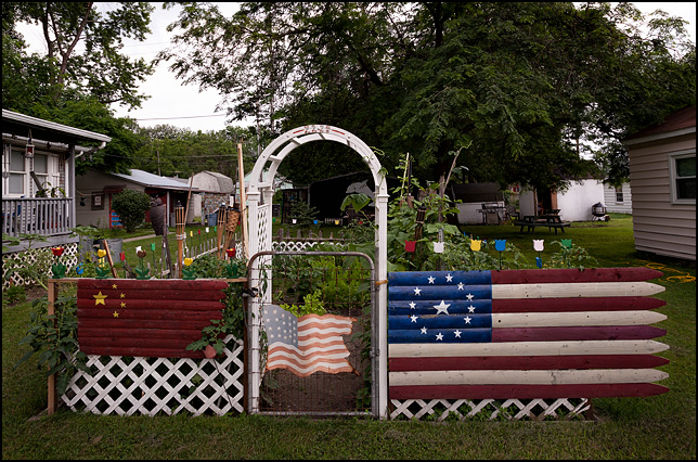 A Chinese flag and an American flag on a fence around a garden in Fort Wayne, Indiana. Wooden tulips stand atop the fence, and a painted metal American flag hangs on the gate.