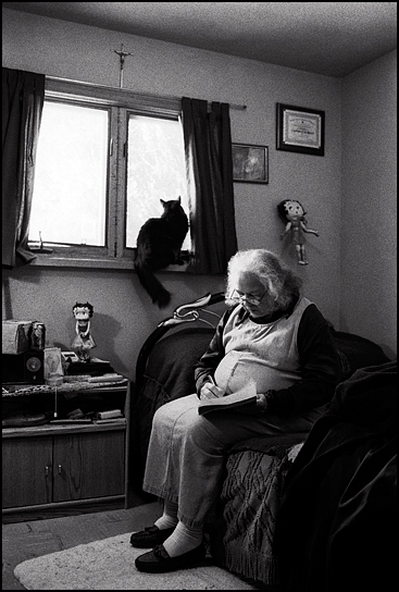 Christine Apodaca, an elderly Hispanic woman, sits on her bed writing letters while her black cat sits in the window behind her. She has two Betty Boop dolls and a crucifix on the wall.