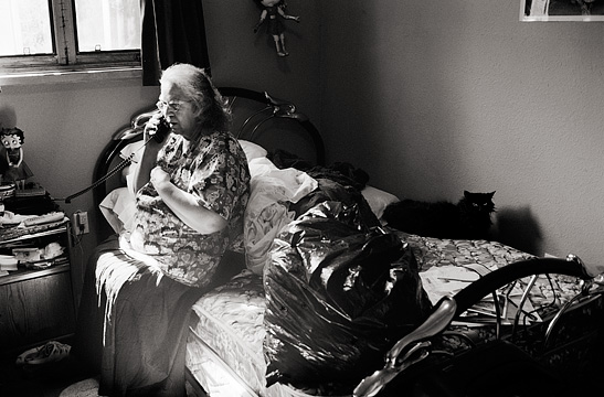 An elderly woman sits on her bed while talking on the telephone while her black cat stares at me with evil eyes from the bed behind her. Christine Apodaca.
