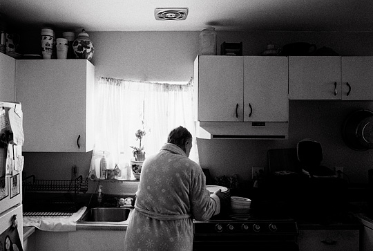 An elderly woman wearing a bathrobe washes dishes in her kitchen.