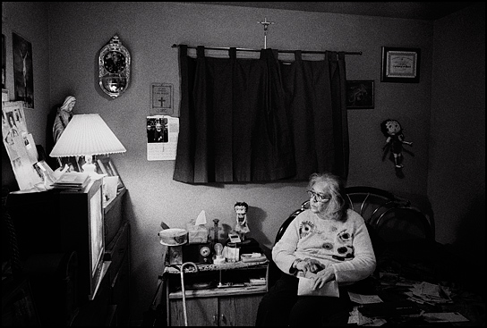 An elderly woman sits in her bedroom opening the mail and watching television. She is a devout Catholic with crosses and statues of the Virgin Mary all over the walls. She also has two Betty Boop dolls.