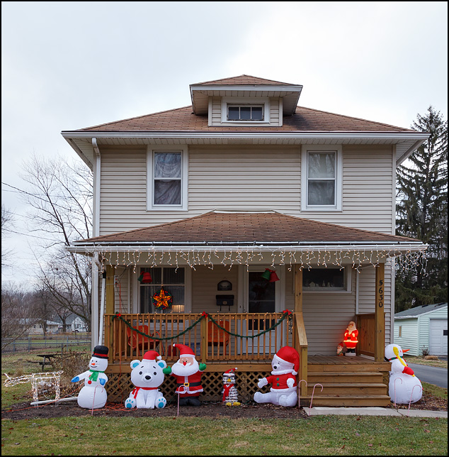 Inflatable Christmas decorations in front of a house on Woodheath Avenue in Fort Wayne, Indiana. The inflatables include Santa Claus, polar bears, and snowmen.
