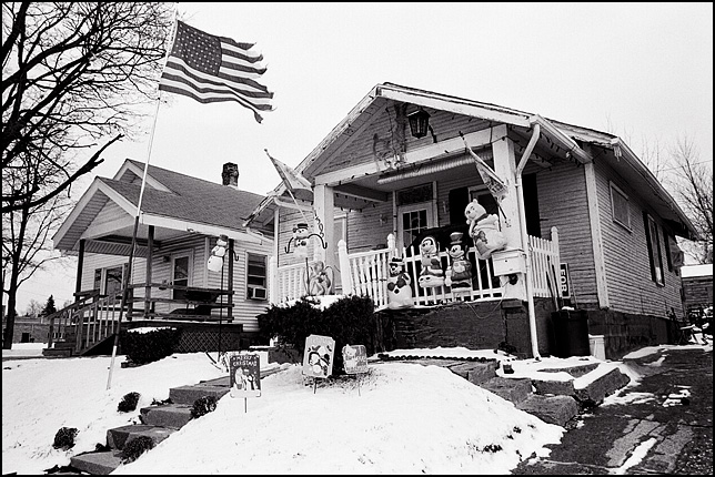 A little bungalow covered in Christmas decorations and plastic snowmen with a tattered American flag flying from a flagpole in the snow covered yard on Warren Street on the east side of Fort Wayne, Indiana.