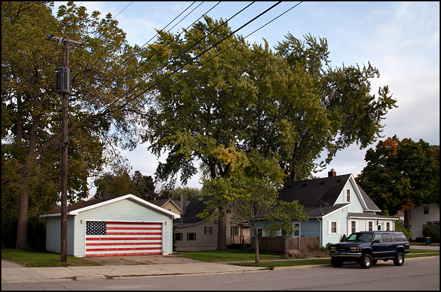A large handpainted American flag completely covers the front door of a garage behind a house on Christyann Street in Mishawaka Indiana.