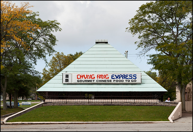 Chung King Express, a Chinese restaurant in a small pyramid shaped building that was originally built as a branch of People's Trust Bank in Fort Wayne, Indiana. The owner is standing by the door watching me.