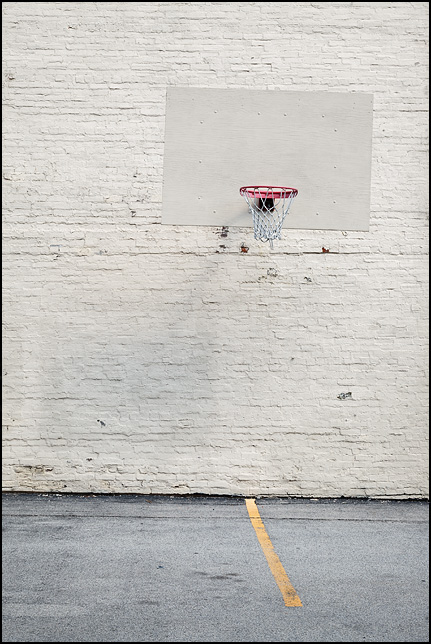 A basketball hoop on an old brick wall in the barking lot behind the Warren Church of Christ in the small town of Warren, Indiana.