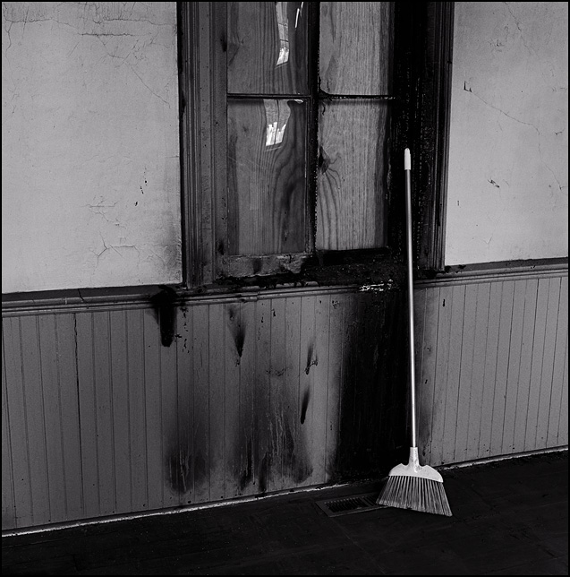 A broom leans against a charred wall and boarded up window in the Prairie Grove Cemetery Chapel during reconstruction work after it was burned by Vandals.