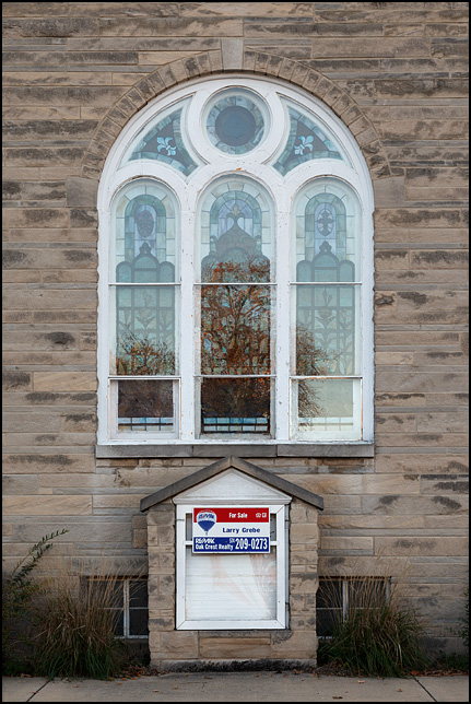 A vacant church building with a real estate agents For Sale sign. The limestone church is the former Bremen United Methodist Church on Montgomery Street in the small town of Bremen, Indiana.