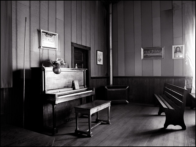 An old upright piano and pews at the front of the Lawton Christian Church in rural Pulaski County, Indiana. An old gas heater sits in the corner of the dilapidated church and pictures of Jesus Christ and the last supper hang on the walls.