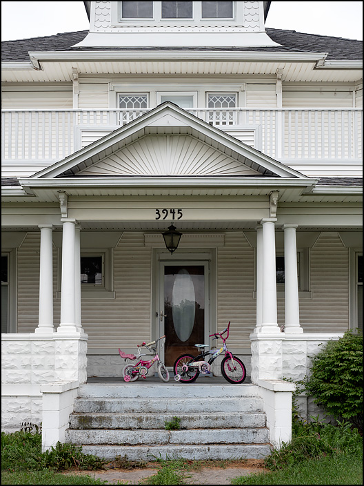 Two small child-sized bicycles on the front porch of a large white Victorian house on US-33 in the small town of Churubusco, Indiana.