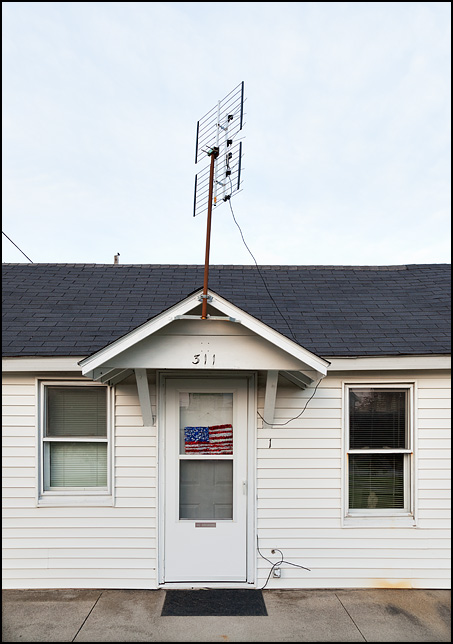 A small white house on Main Street in the small town of Churubusco, Indiana. The front door is decorated with an American flag made of garland and there is an old TV antenna mounted on a pole above the door.