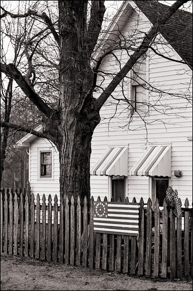 A hand-painted American flag and a patriotic ribbon on a picket fence around a white house on Mulberry Street in the small town of Churubusco, Indiana.
