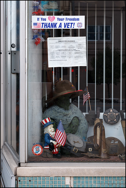 The front window of the Veterans of Foreign Wars Post in the small town of Churubusco, Indiana. The window is full of old war memorabilia and an Uncle Sam lawn gnome holds a small American flag. A bumper sticker on the window says, If you love your freedom thank a vet.
