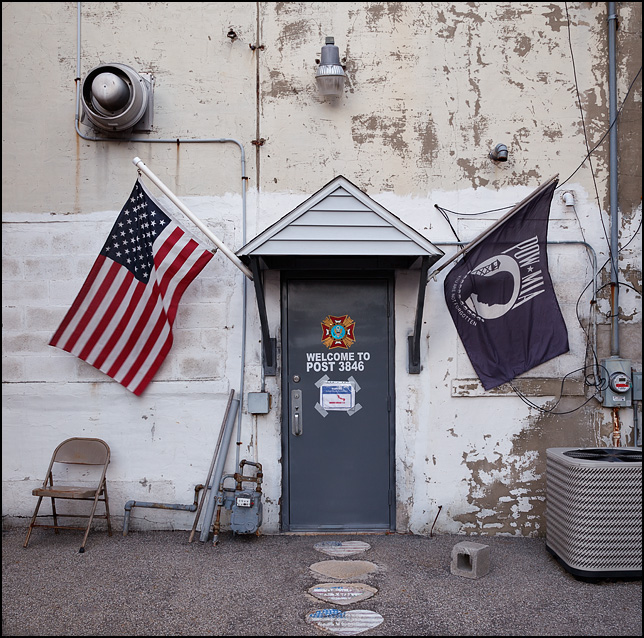 An American flag and a POW-MIA flag hang beside the door in the alley behind the Veterans of Foreign Wars Post in the small town of Churubusco, Indiana. Heart shaped stepping stones on the ground are painted like the American flag and a folding chair sits beside the door.