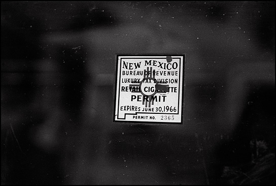 "A sticker that says: ""New Mexico Department of Revenue Luxury Tax Division Retail Cigarette Permit. Expires June 30, 1966"" on the glass display case at Mary's Bar in Cerrillos, New Mexico."