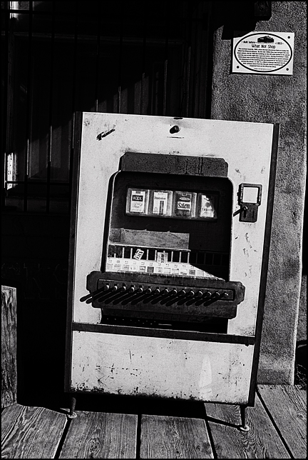 An old broken cigarette machine on the front porch of the What Not Shop in Cerrillos, New Mexico.
