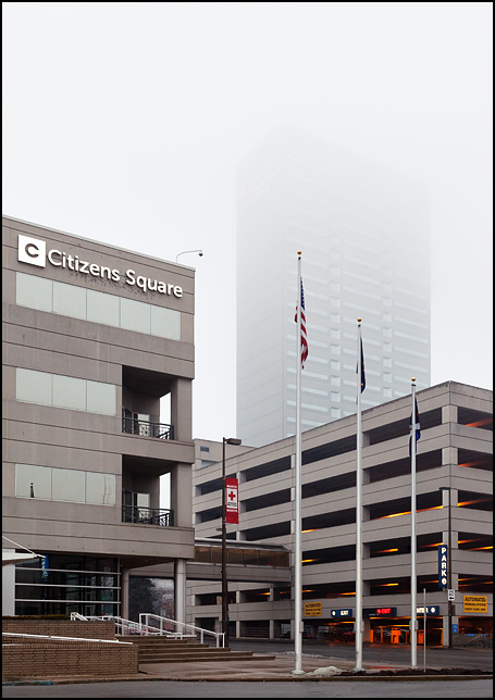 The Citizens Square government building and the One Summit Square skyscraper on a rainy evening in downtown Fort Wayne, Indiana. The top half of the One Summit Square tower is shrouded in heavy fog.