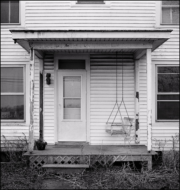 A porch swing by the front door of an old white farmhouse in rural Allen County, Indiana.