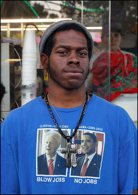 An African-American man wearing a t-shirt comparing Bill Clinton and Barack Obama. President Clinton - Blow Jobs. President Obama - No Jobs. He is also wearing two necklaces with large cross pendants.