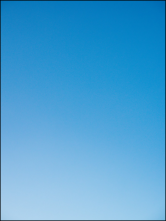 Abstract color field photograph of a blue sky that shifts toward white at the bottom.