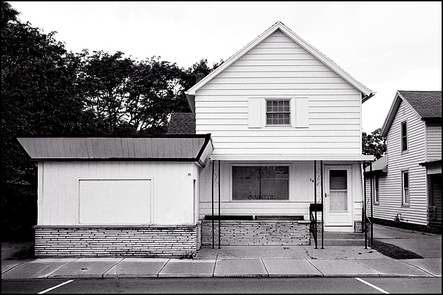 An old house with a boarded up storefront on Wells Street in Fort Wayne, Indiana.