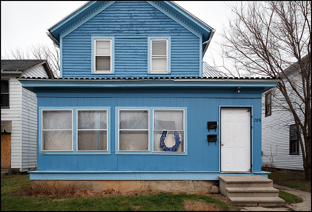 A house painted blue and white, the colors of the Indianapolis Colts, with a large Colts logo in the front window. The house is on Third Street in Fort Wayne, Indiana.