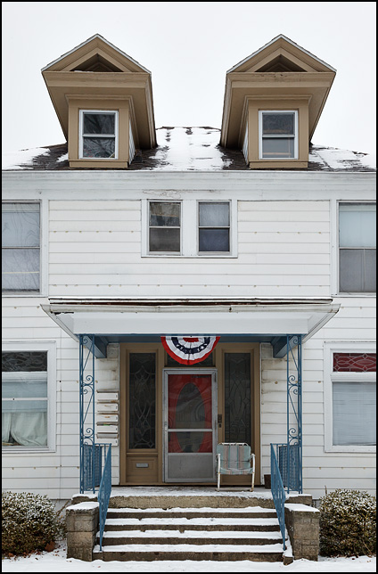 A single chair sits next to the door on the front porch of a large old house on Columbia Avenue in Fort Wayne, Indiana. Patriotic bunting hangs from the porch.