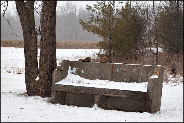 Color photograph of a big concrete bench that looks like a church pew sitting near a cornfield along the side of Dalman Road in rural Allen County, Indiana.