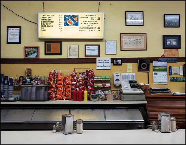 The counter at Fort Wayne's Famous Coney Island Hot Dog Stand. An old Hynap napkin holder sits on the counter, and racks of potato chips stand under the menu sign behind it.