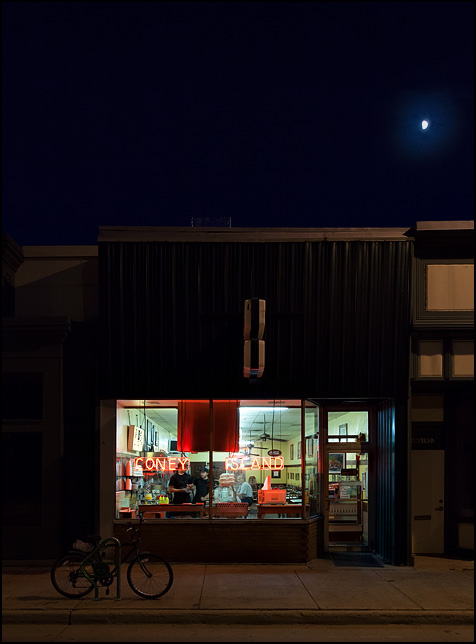 The front windows of Fort Wayne's Famous Coney Island Hot Dog Stand late at night right before closing time. An old man sits at the counter, the last customer of the day.