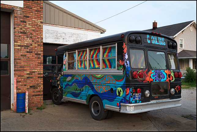 An old short bus painted with psychedelic designs and pictures of planets and UFOs. The sign on the bus says that it is the Cool Bus.