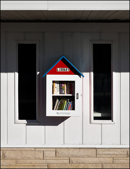 The library in the little village of Corunna, Indiana. It is a Little Free Library hanging on the front of the Town Hall building.