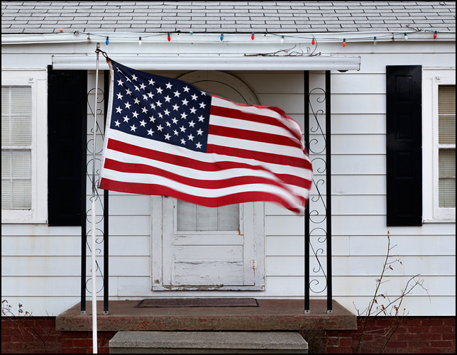 A large American flag blows across the front door of a little house on Covington Road in Fort Wayne, Indiana.