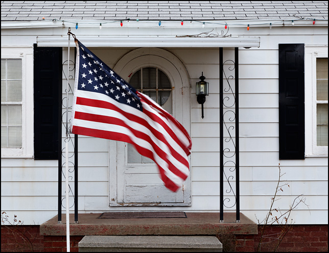 An American flag waves in the wind in front of a house on Covington Road in Fort Wayne, Indiana.