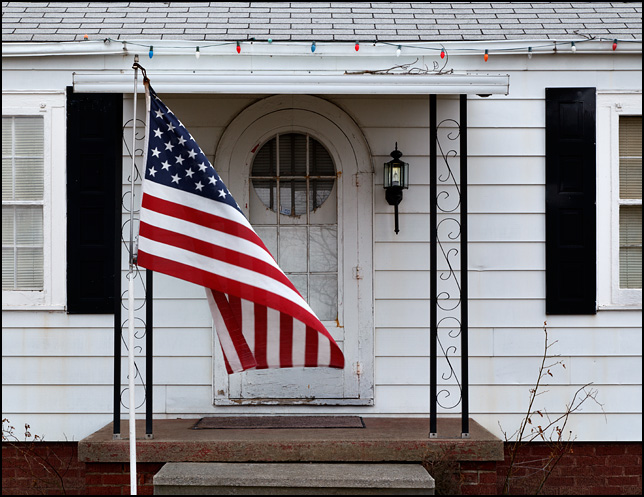 An American flag hangs limp in front of a house as the wind begins to blow.