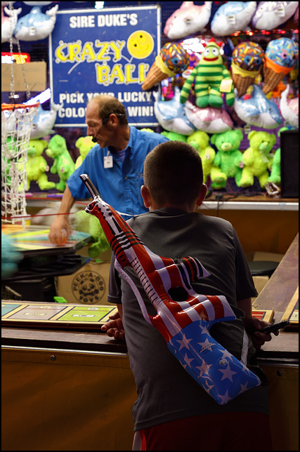 A boy with an inflatable assault rifle that he won at the 2016 Elkhart County Fair in Goshen, Indiana. He is watching a game called Sire Dukes Crazy Ball. The inflatable gun is colored like the American flag.