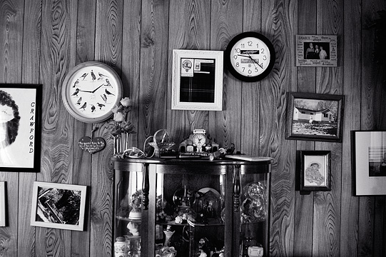 A curio cabinet full of mementos sits in front of a paneled wall in my grandparents house. The wall is covered in framed photographs and has two clocks.
