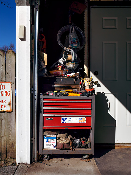 My fathers old red Craftsman tool chest in his garage. A smaller toolbox sits on top of the cabinet, and tools are piled high on both tool chests. The big chest has an Indiana Air National Guard bumper sticker on it.