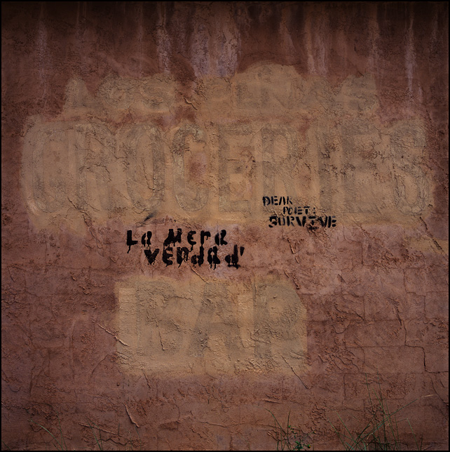 Graffiti that says Dear Poet Survive and La Mera Verdad painted on the adobe wall of the abandoned Los Penas grocery store in Encino, New Mexico.
