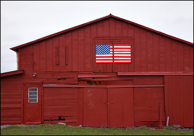 A red barn with a handpainted American flag on plywood hanging over the doors on County Road 5 in rural Dekalb County, Indiana.