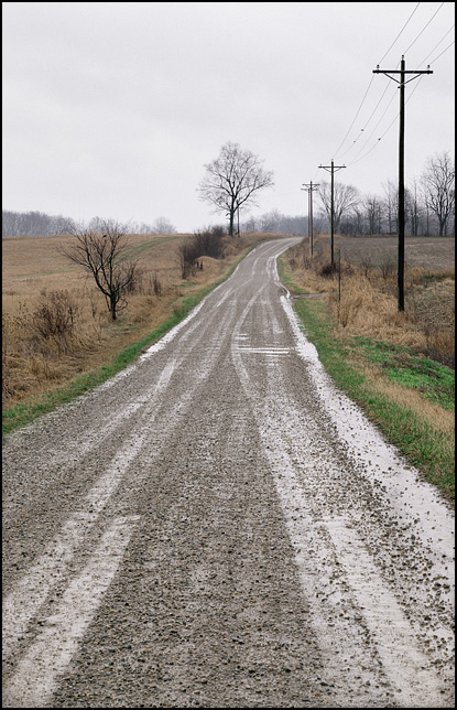 A gravel road running through hilly farmland on a rainy morning in rural Indiana.