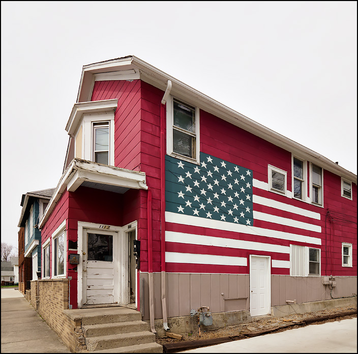A large American flag painted on the side of an old red apartment house on Delaware Avenue in Fort Wayne, Indiana.