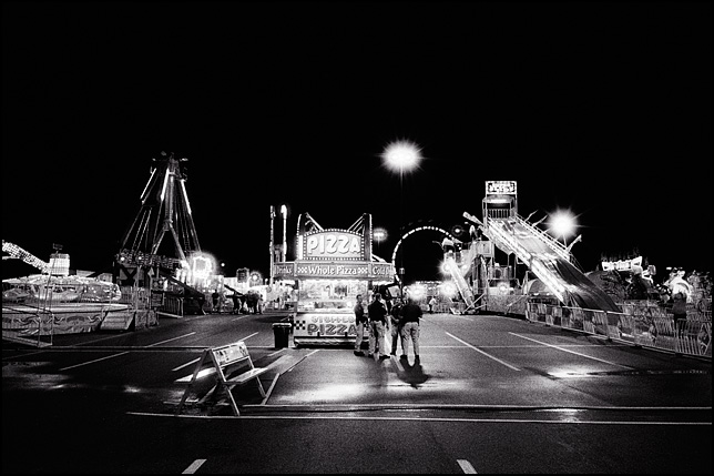 A brightly lit nighttime carnival with no people except for a few police officers standing in front of the pizza concession.